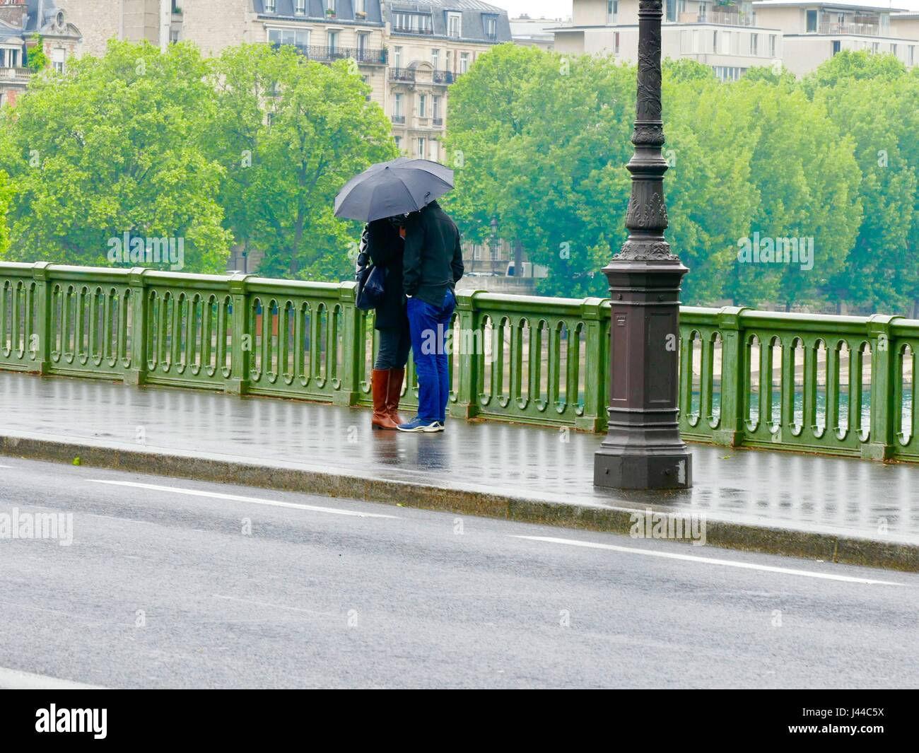 lovers-under-an-umbrella-on-a-bridge-ove
