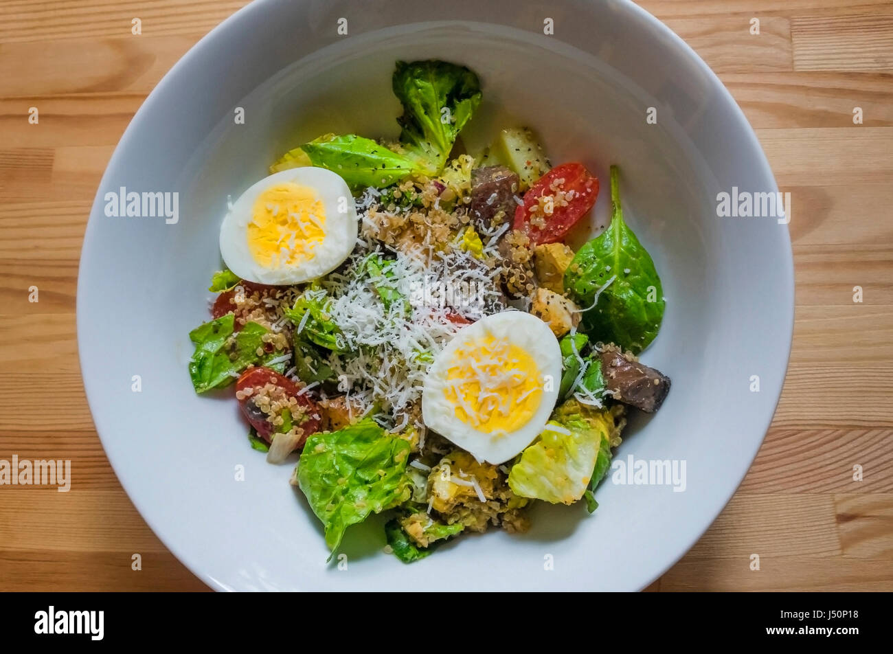 a-mixed-green-salad-in-a-white-bowl-on-a