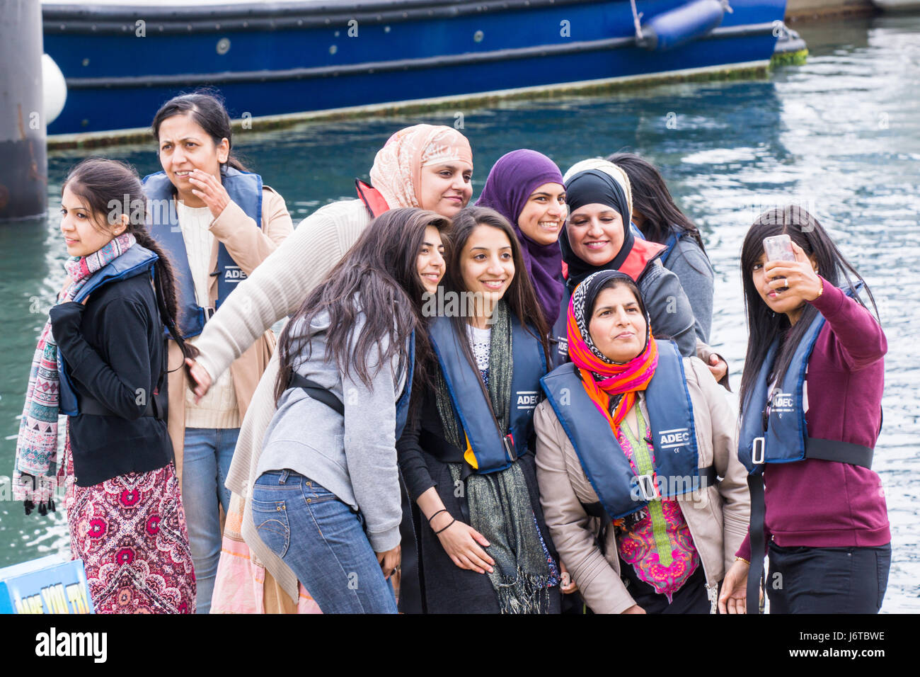 Group of women wearing life vests taking a selfie on their phone before going for a boat cruise at Scarborough, Stock Photo