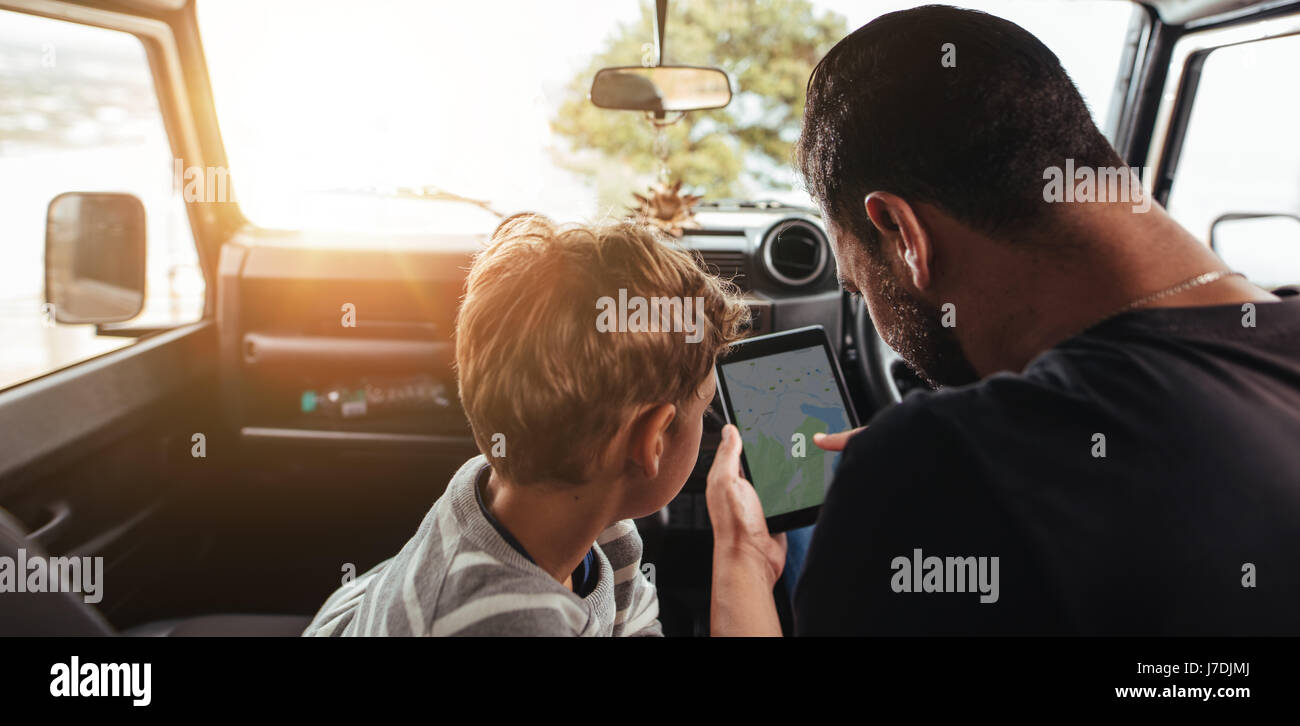 Close up rear view of father and son looking at map on digital tablet while travel by car. Family looking for road - Stock Image