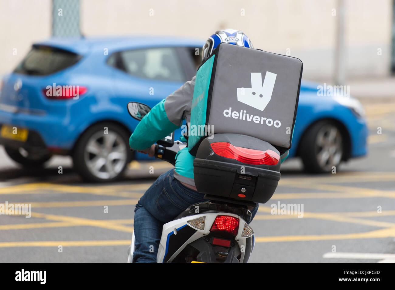 A Deliveroo rider on a moped making a food delivery in Cardiff, Wales, UK. Stock Photo