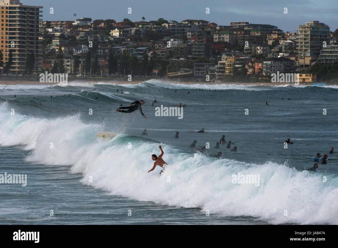 Dramatic scene with surfer flying high in the air at Manly beach, Sydney, New South Wales, Australia Stock Photo