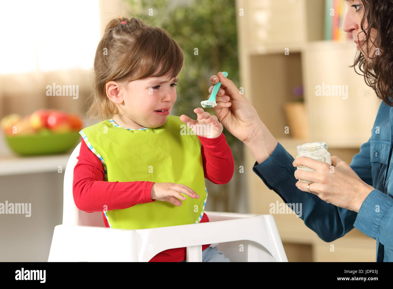 Toddler crying at lunch time sitting in a highchair in the living room at home with a homey background Stock Photo