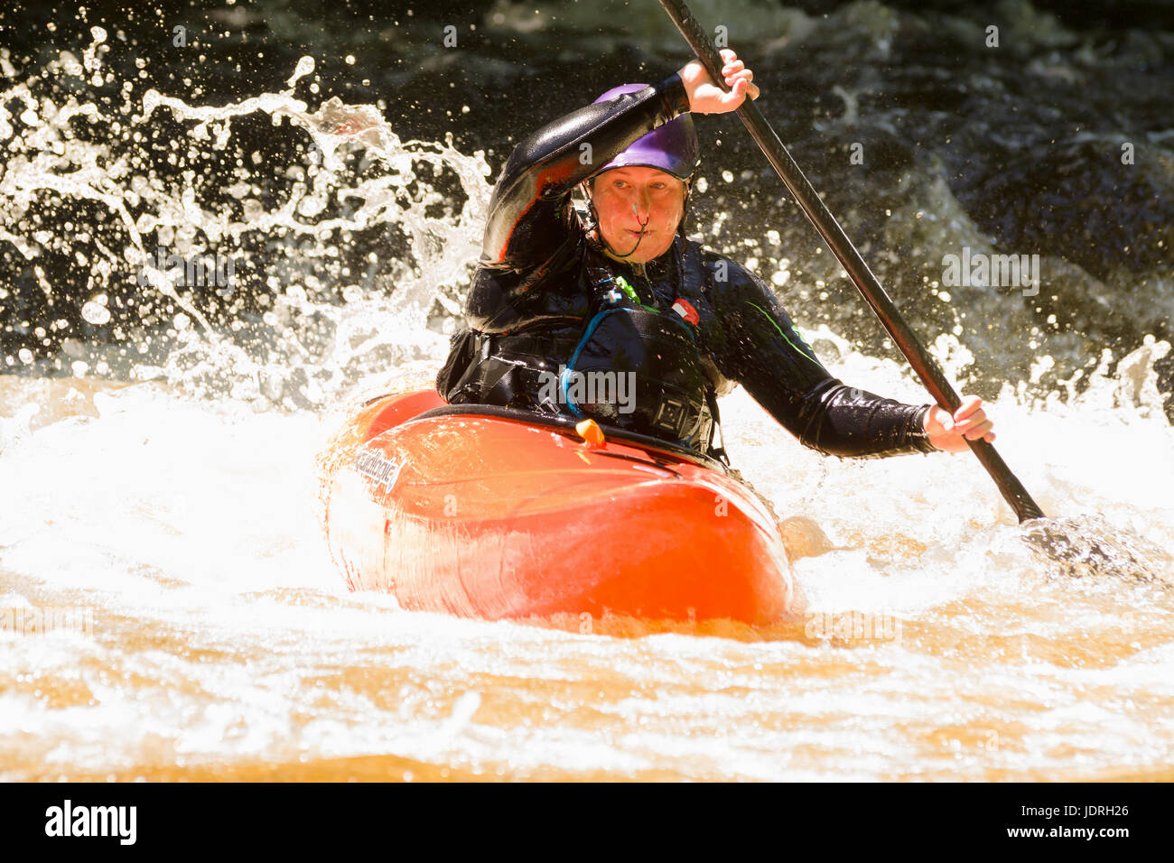 White water kayaker shooting the rapids at the National White Water Centre on the River Tryweryn in Snowdonia National Stock Photo