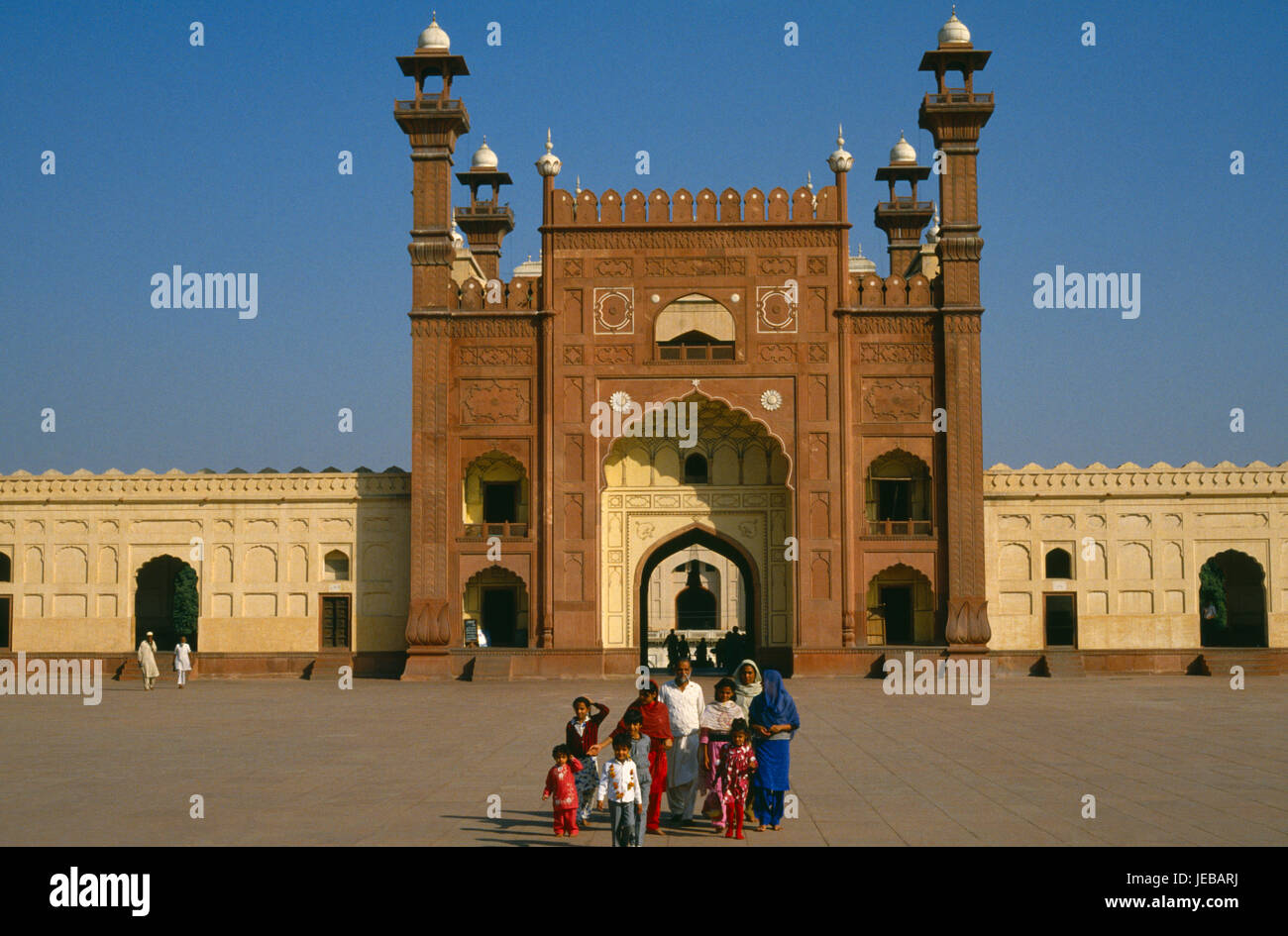 Pakistan, Punjab, Lahore, Badshahi mosque. Family standing in courtyard outside entrance of mosque attached to the - Stock Image
