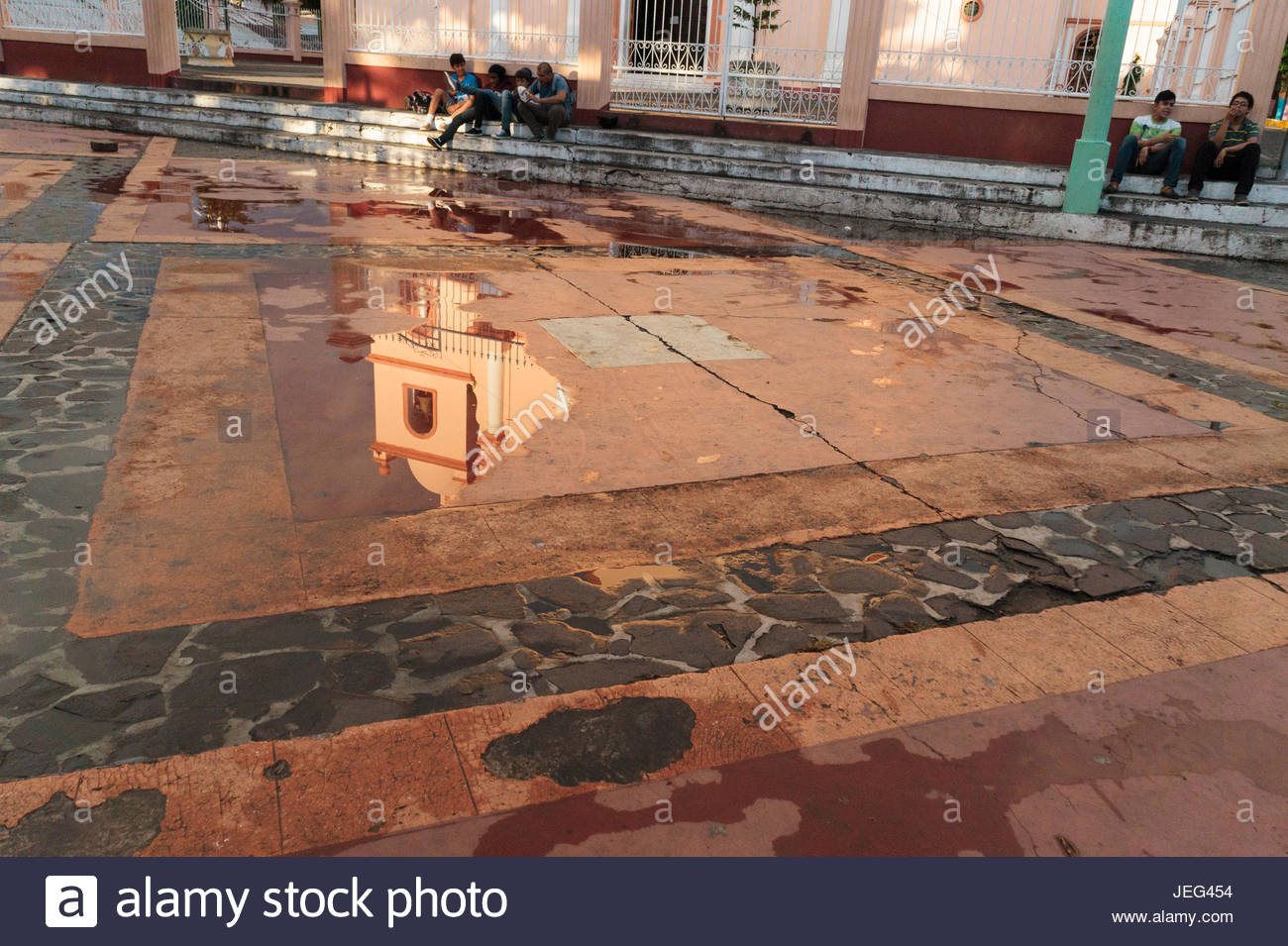 Church reflected in rain puddles on the church plaza, Boaco, Nicaragua. Stock Photo