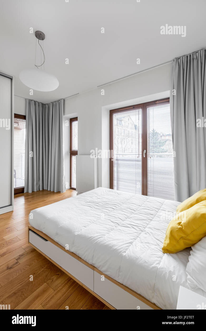 White Bedroom With Double Bed, Big Balcony Windows And Modern Lamp