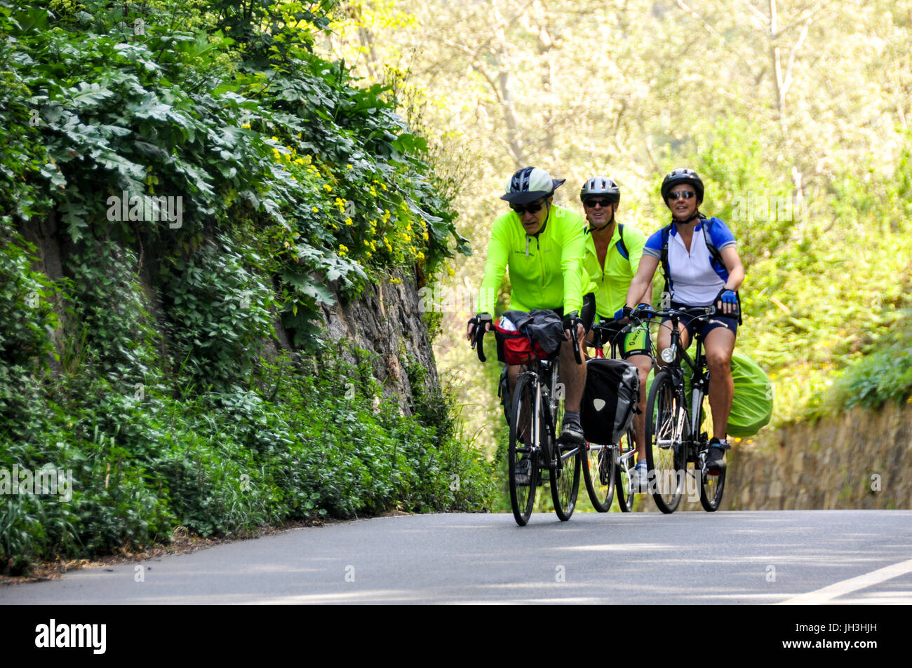three-touring-cyclists-riding-their-bicycles-on-a-country-road-in-JH3HJH.jpg