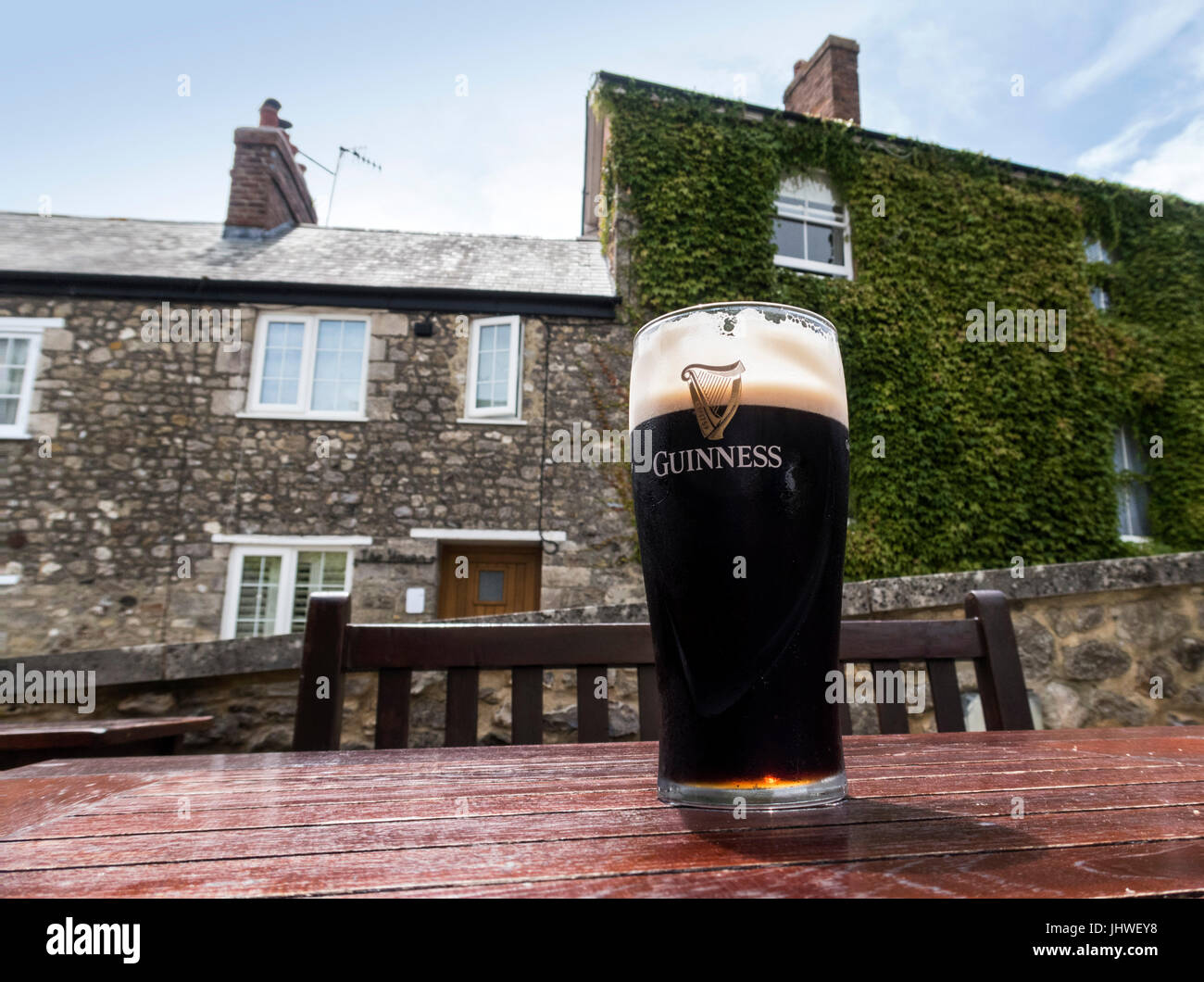 A pint of Guinness on a table outside a country pub. Stock Photo