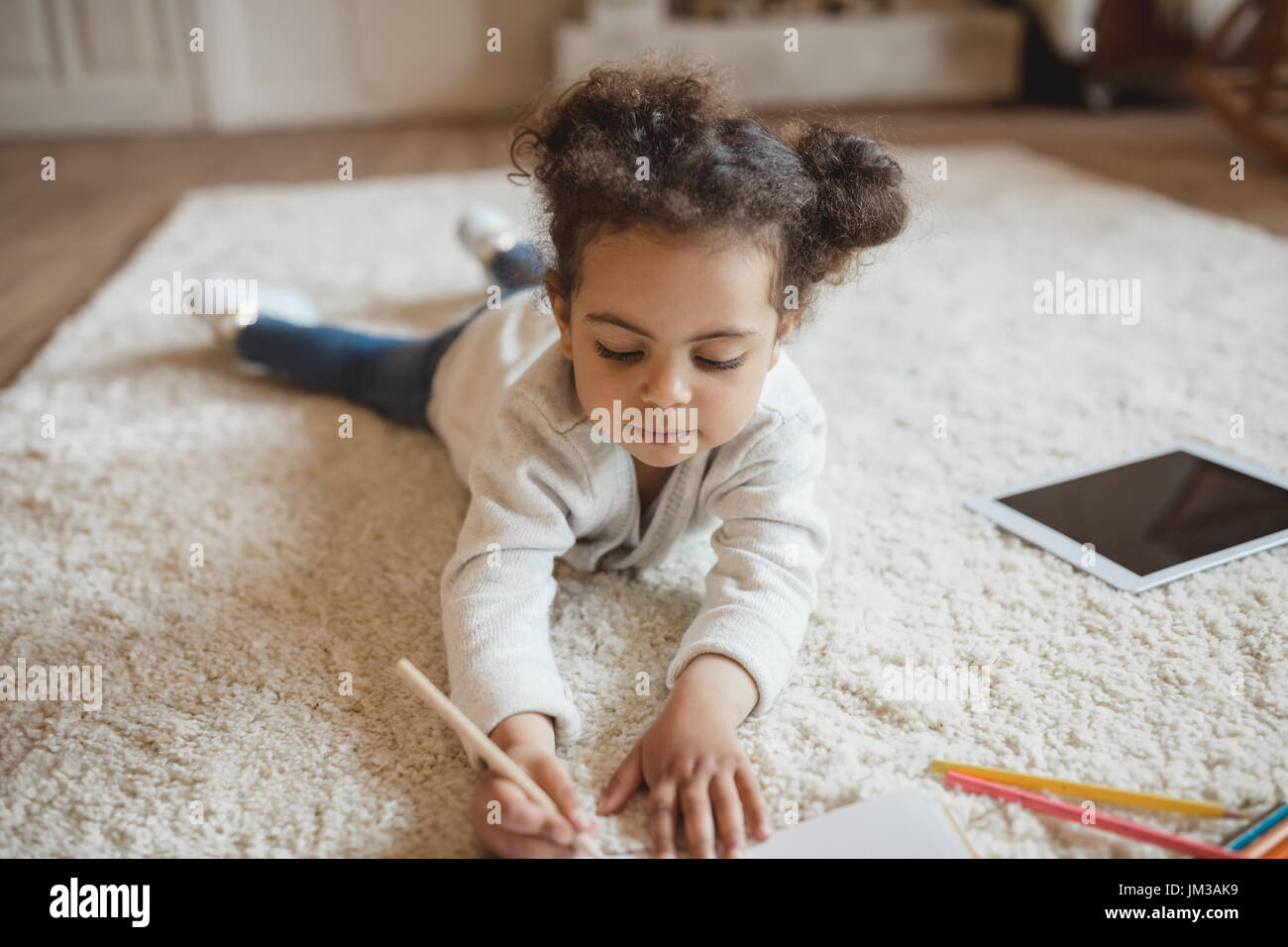 adorable little african american girl drawing with pencils and lying on carpet at home - Stock Image
