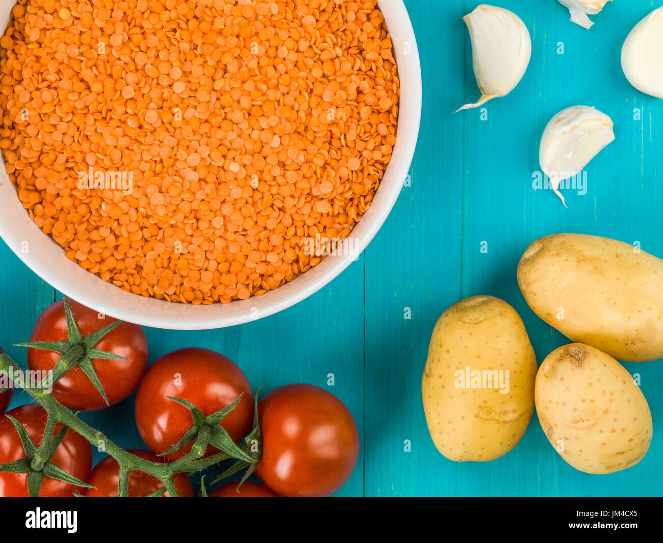 Bowl of Dry Uncooked Red Lentils Against a Blue Wooden Background - Stock Image