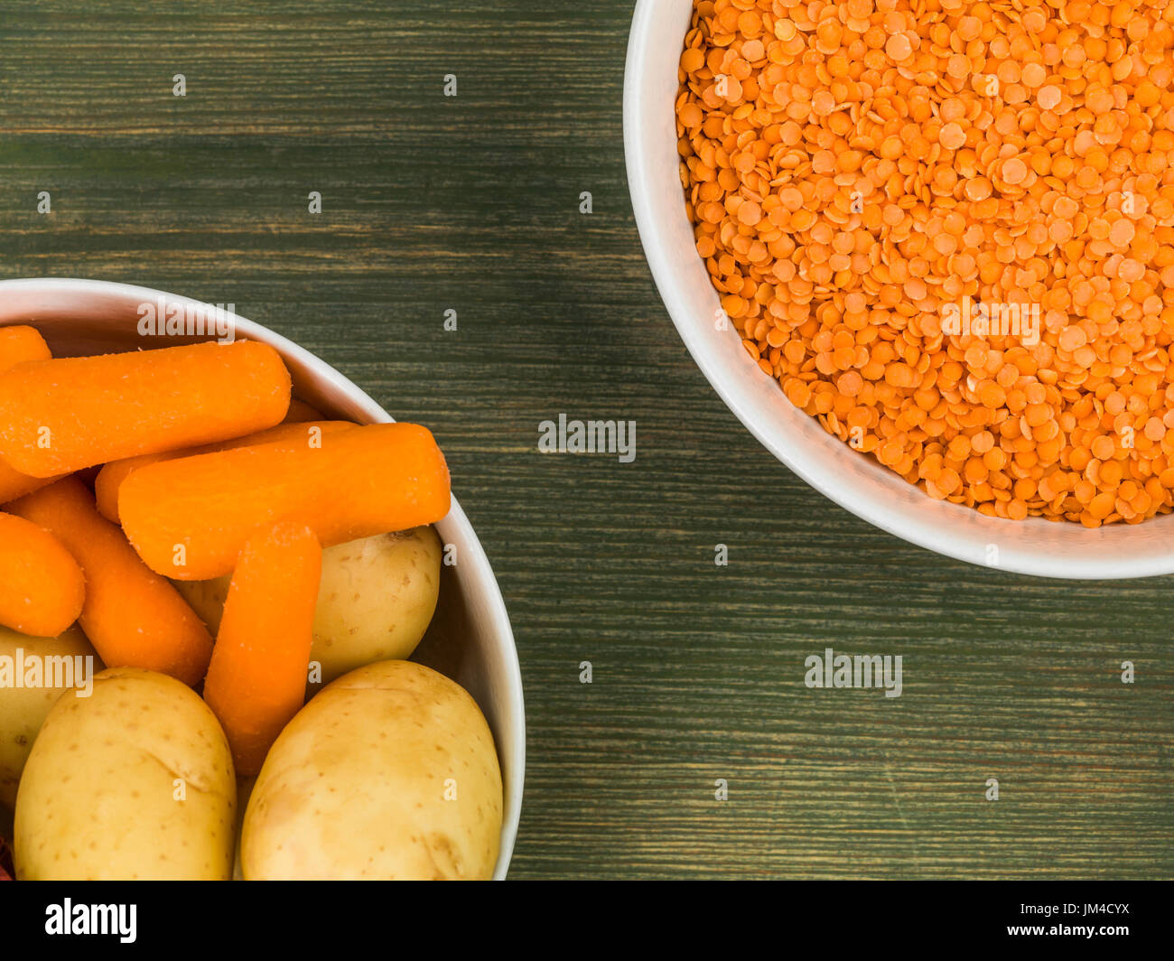 Bowl of Dry Uncooked Red Lentils Against a Green Wooden Background - Stock Image