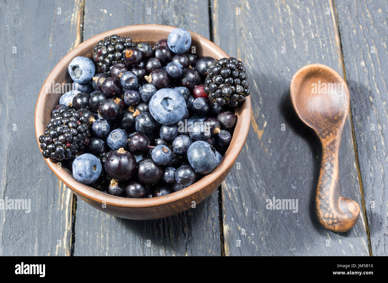Set of pottery with forest berries. Cold mood. Dark decoration. - Stock Image