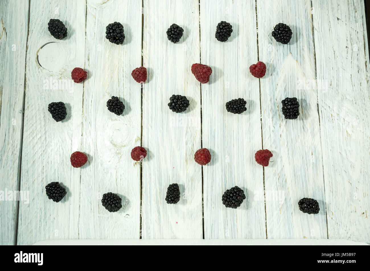 Blackberry and raspberries. are arranged in a row. Flat lay. Berries on a white background. - Stock Image