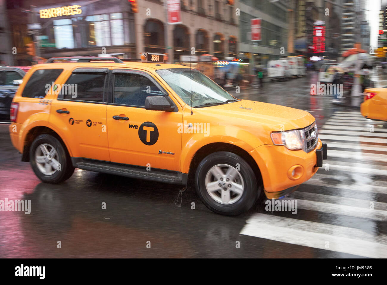Ford escape hybrid suv new york yellow taxi cab crossing times square in the rain new york city usa