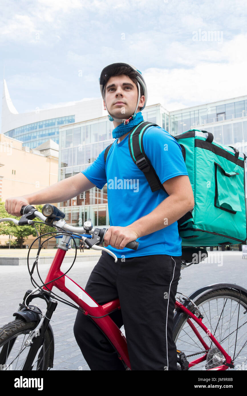 Courier On Bicycle Delivering Food In City - Stock Image