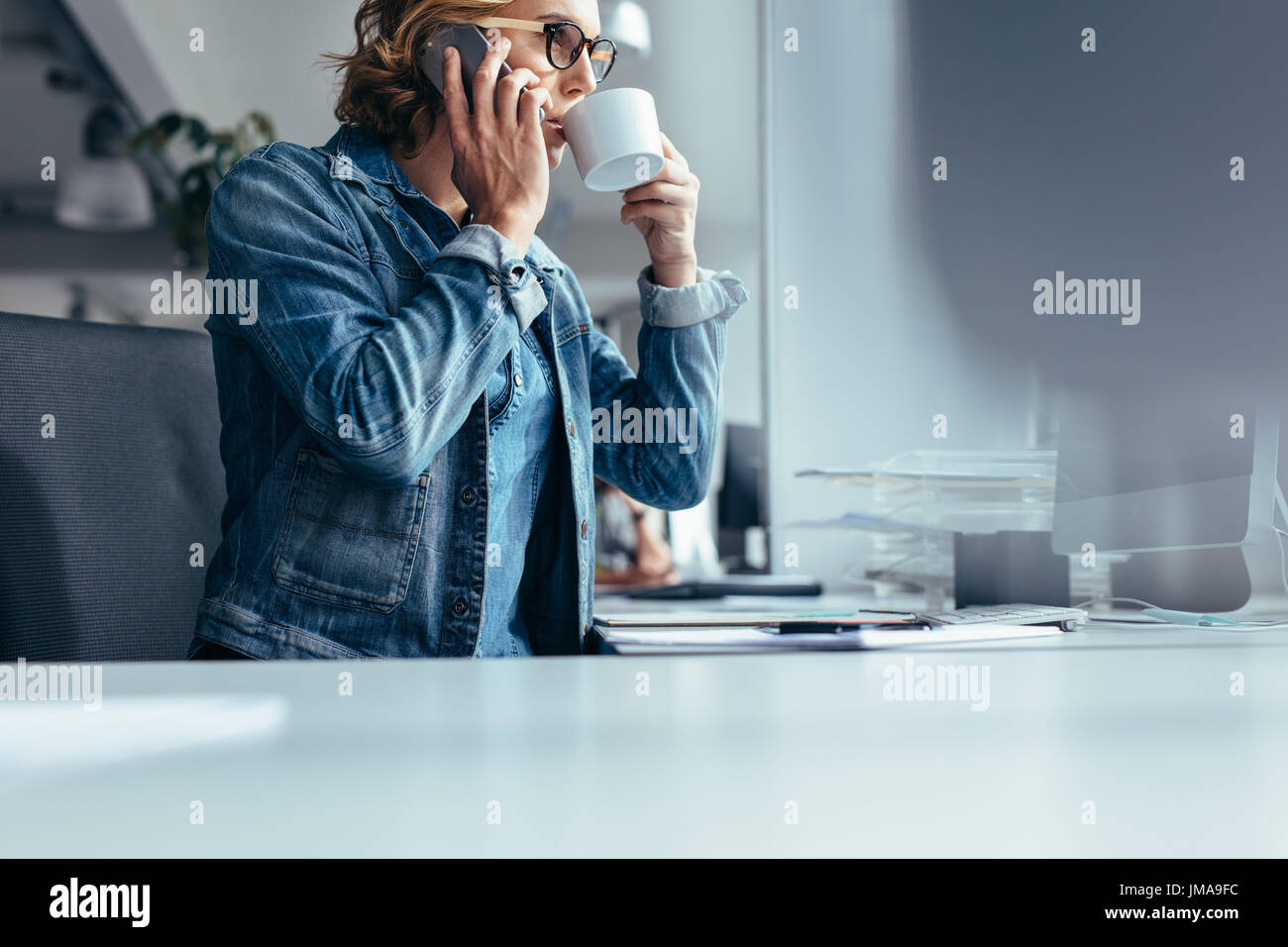Female at work drinking coffee and talking on mobile phone. Young businesswoman at work making phone call and having - Stock Image