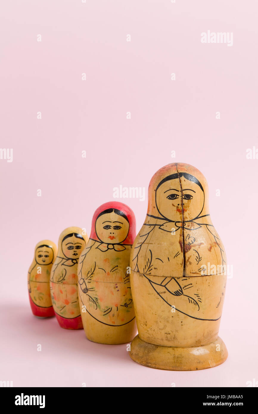 an old matrioshka on a vibrant pink background. Minimal color still life photography - Stock Image