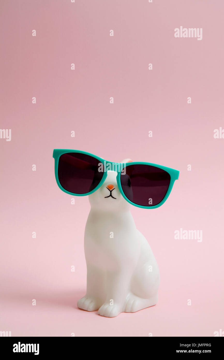 a cute white plastic bunny wearing sunglasses on a pink background. Minimal color still life photography - Stock Image