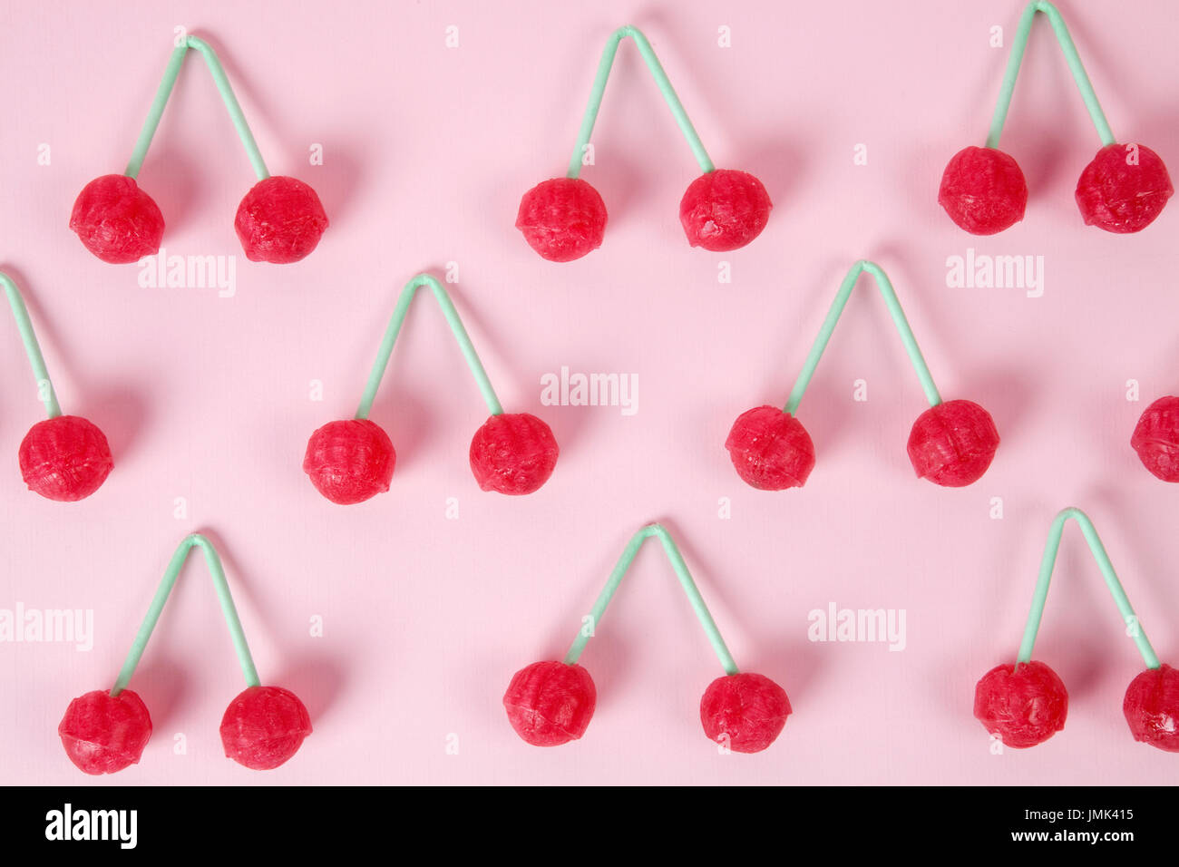 lot of Twin Cherry Lollipops like an old time ago on a pink background with blur effect. Minimal color still life - Stock Image