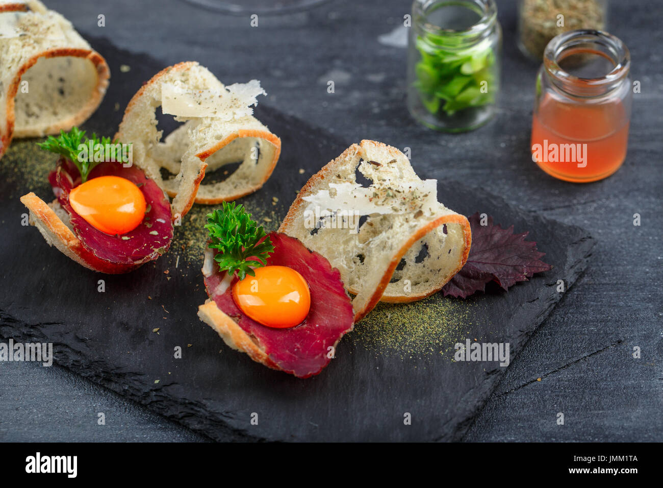 Cured beef on crusty bread with yolk and parmedgano cheese - Stock Image