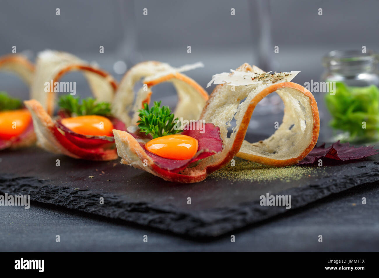Tapas on Crusty Bread - Selection of Spanish tapas served with a sliced baguette. - Stock Image