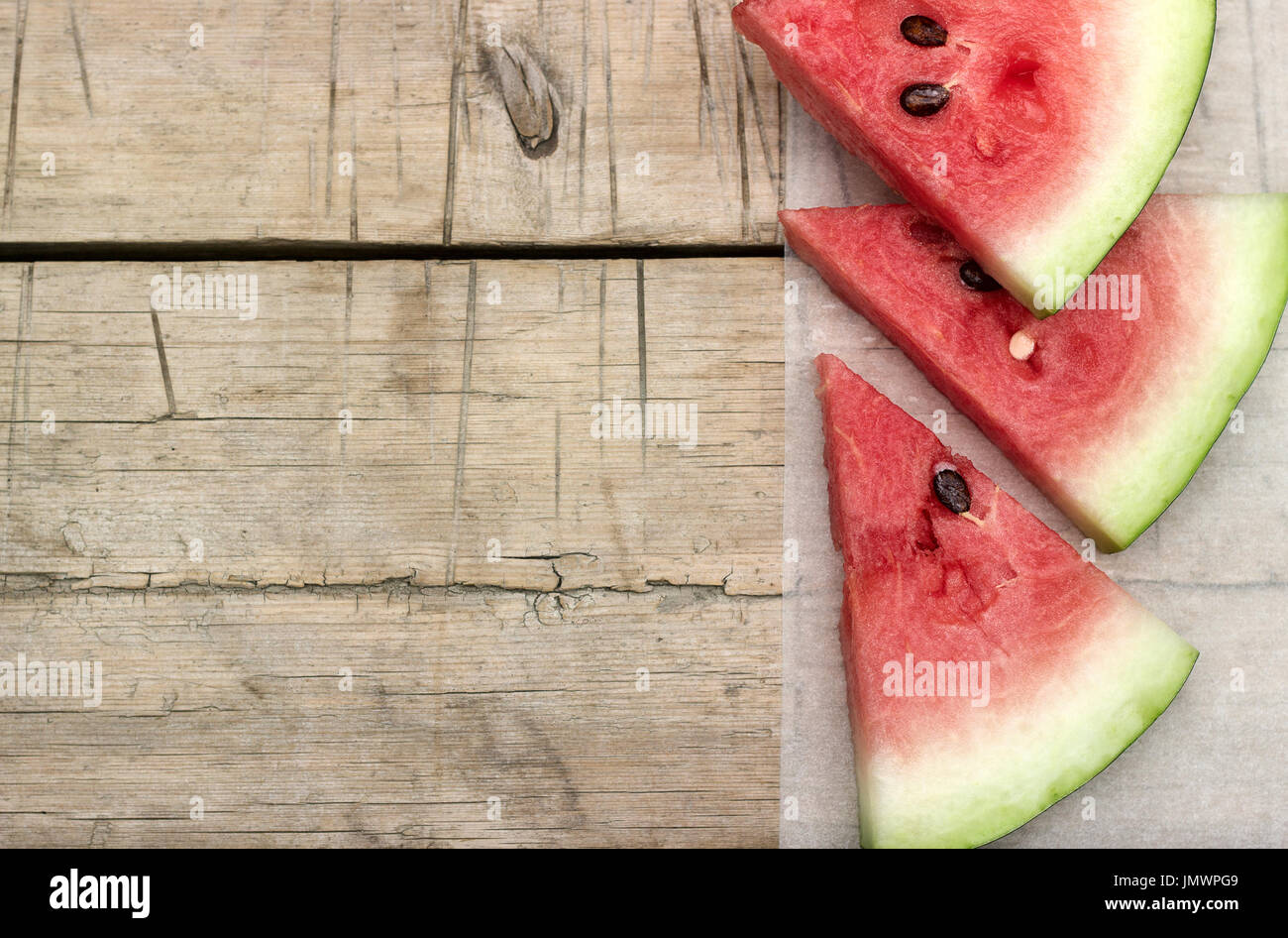 Watermelon slices on a wooden table - Stock Image