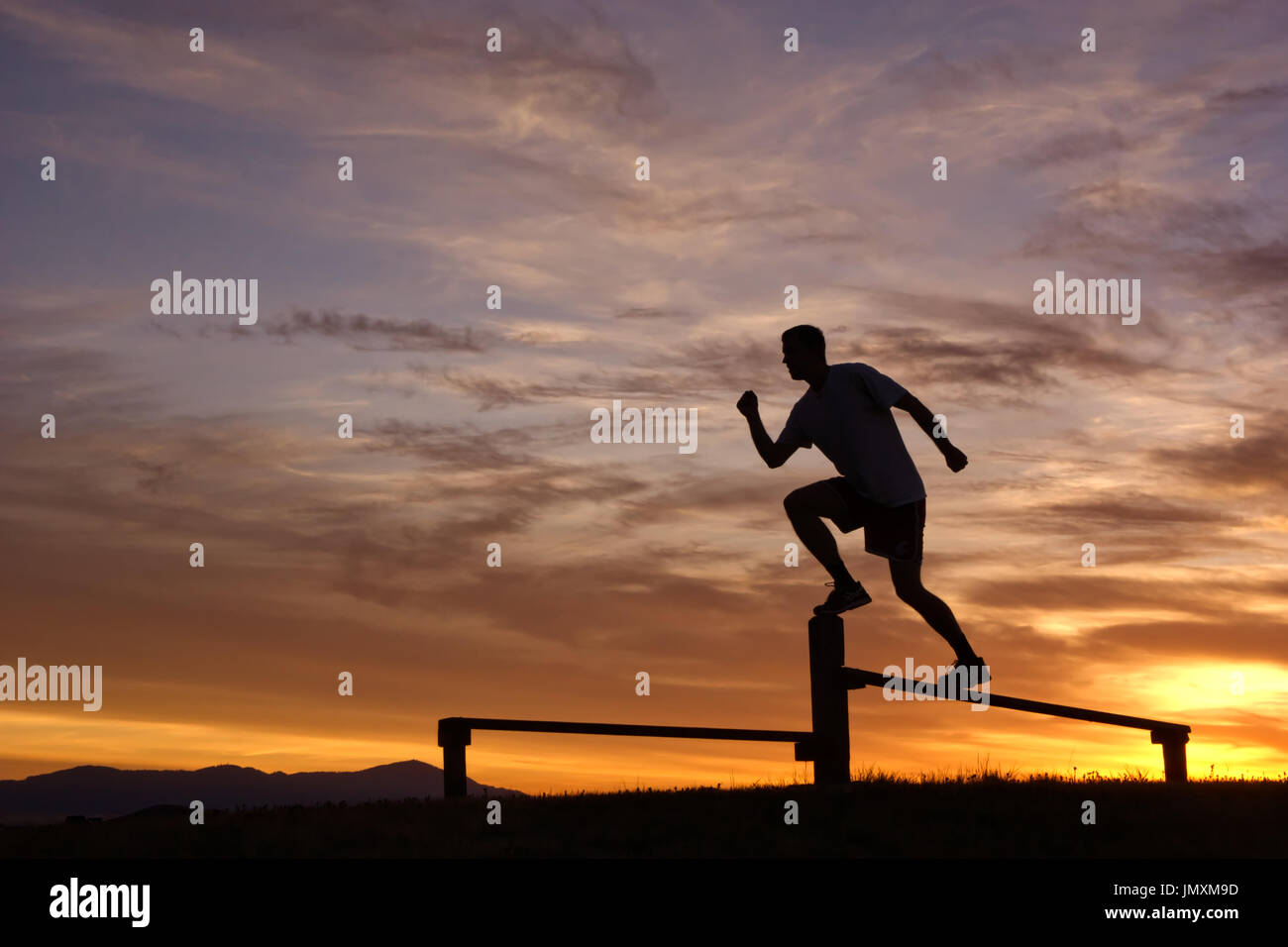 Shadow Runner, Athelete against an awesome sunrise - Stock Image