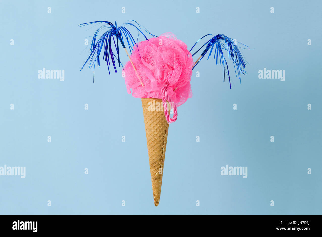 An ice cream cone whose scoop is replaced by a pink plastic loofah sponge. Photographic composition funny and offbeat. - Stock Image