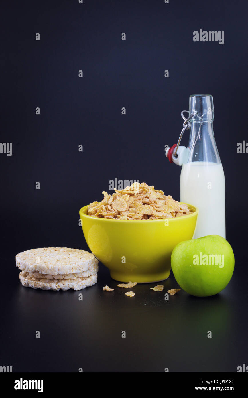 Energy breakfast for diet cereal flakes of corn milk and green apple on black background with copy space - Stock Image