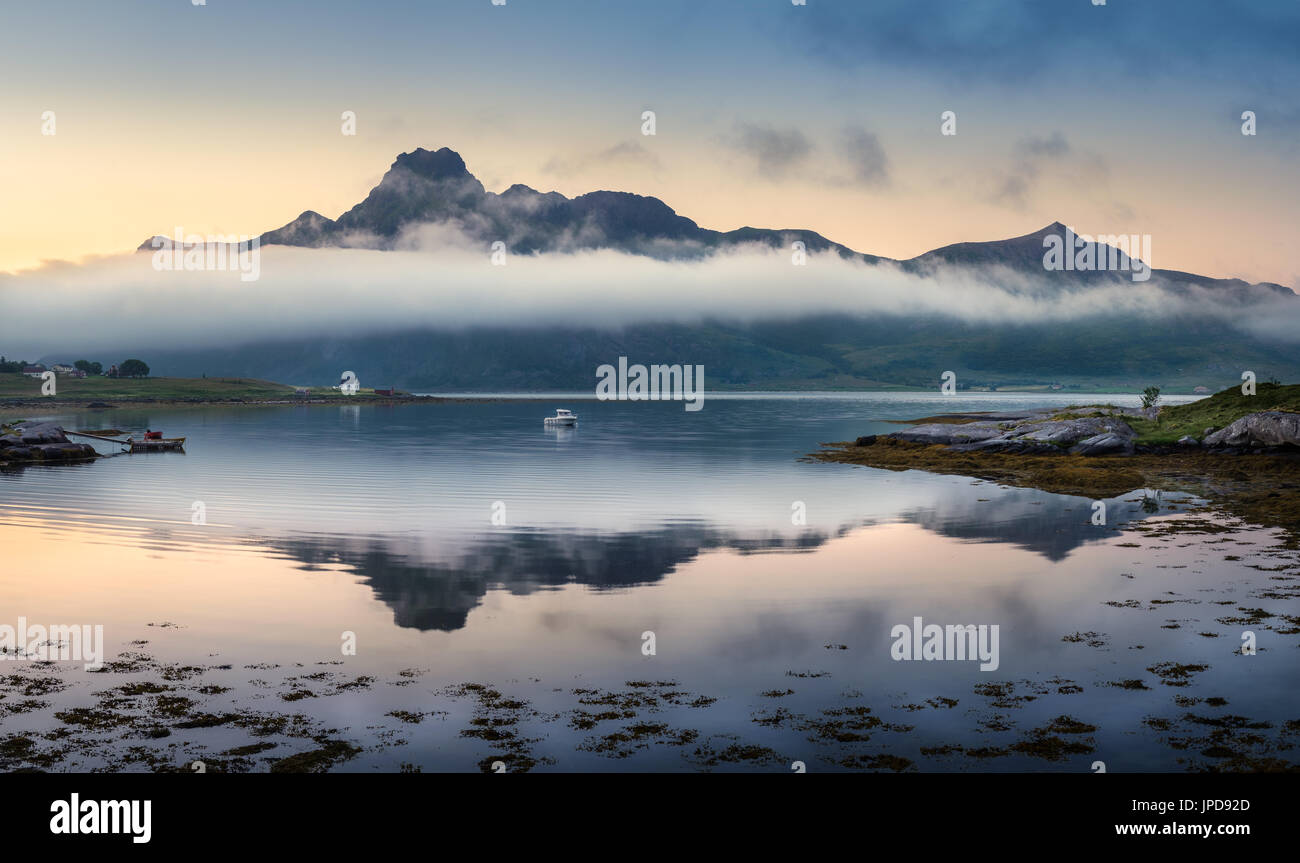 Scenic landscape with mountain reflection and low clouds at summer night in Lofoten, Norway - Stock Image