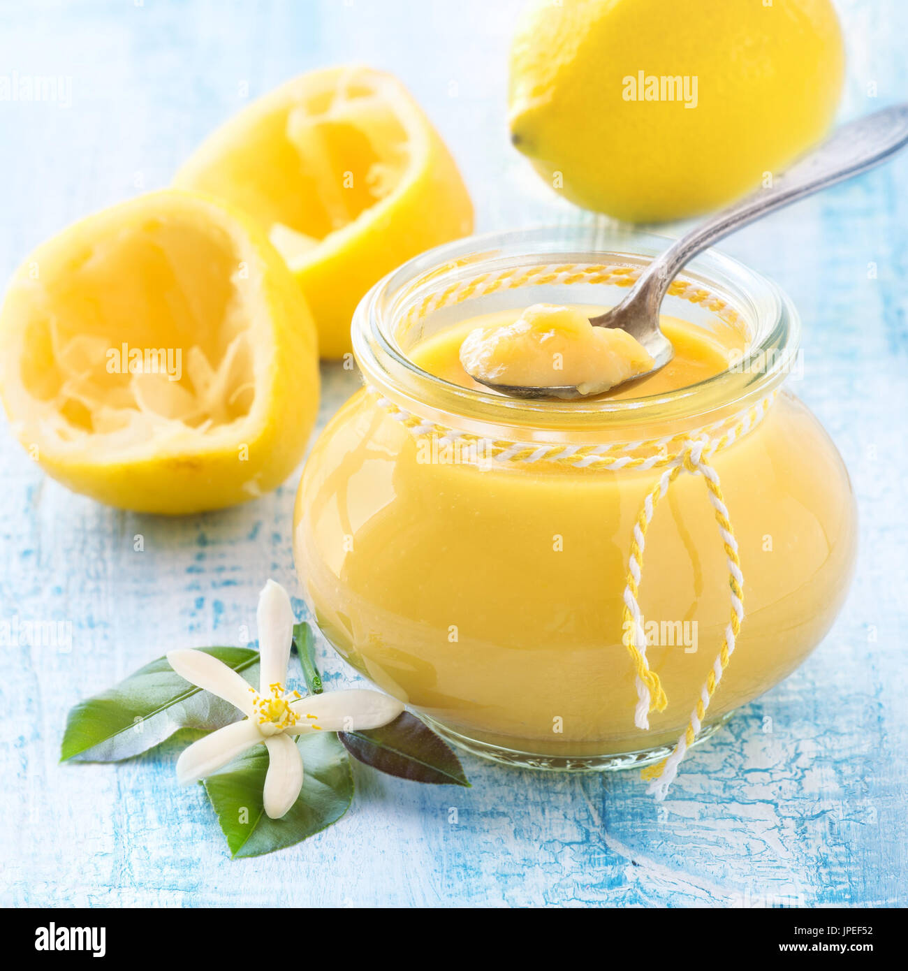 Beautiful banner for web site with delicious homemade lemon curd in a jar and fresh lemons on light blue distressed - Stock Image