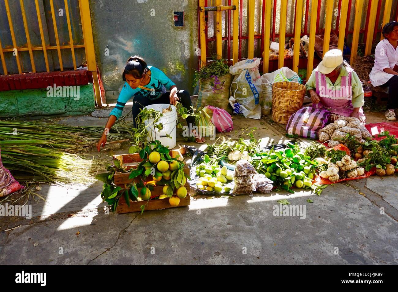 women-selling-produce-on-sidewalk-outsid