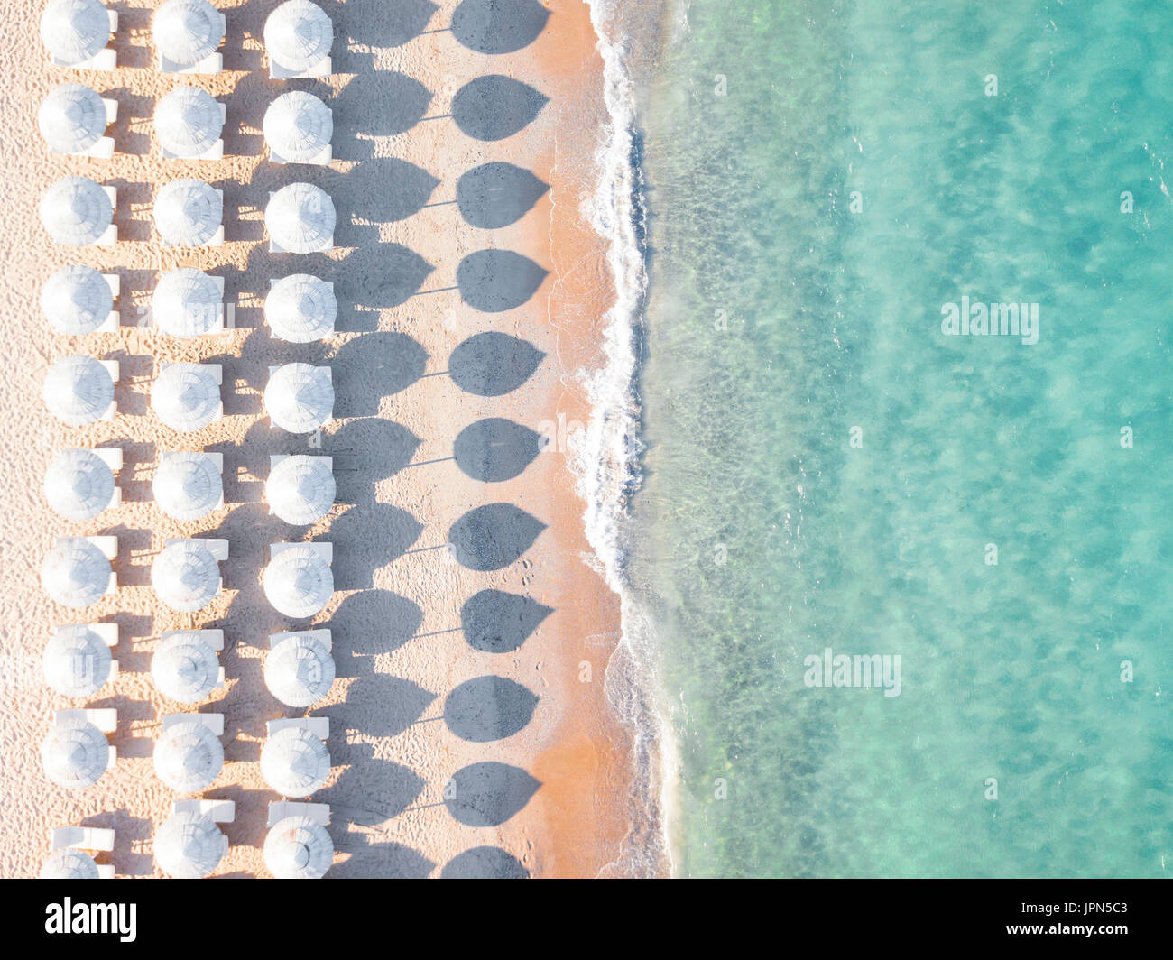 Aerial view of amazing beach with white umbrellas and turquoise sea at sunset. Mediterranean sea, Sardinia, Italy. - Stock Image