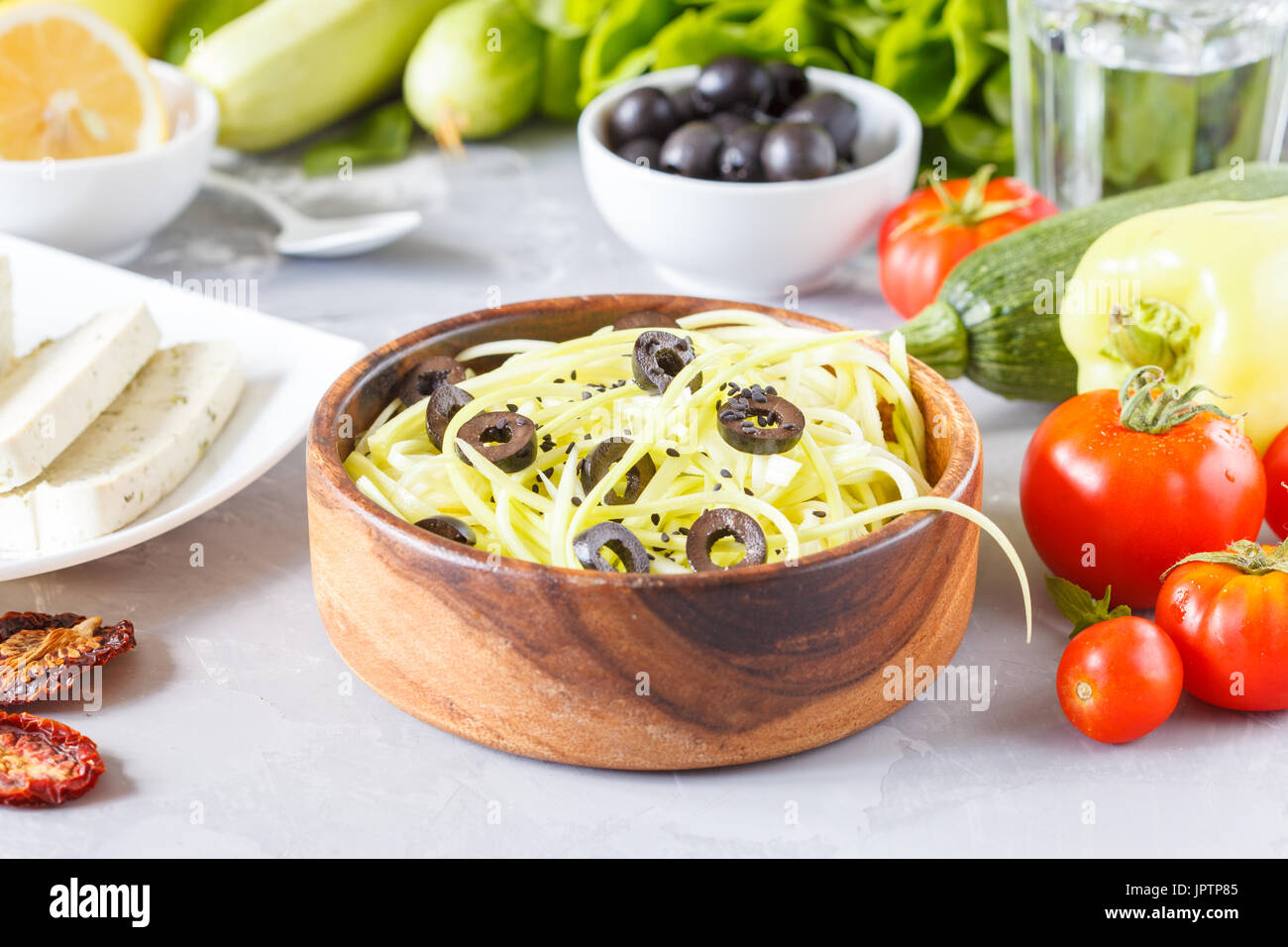 Zucchini pasta with olives and tofu. Vegetarian lunch of vegetables and tofu. Love for a healthy vegan food concept. - Stock Image