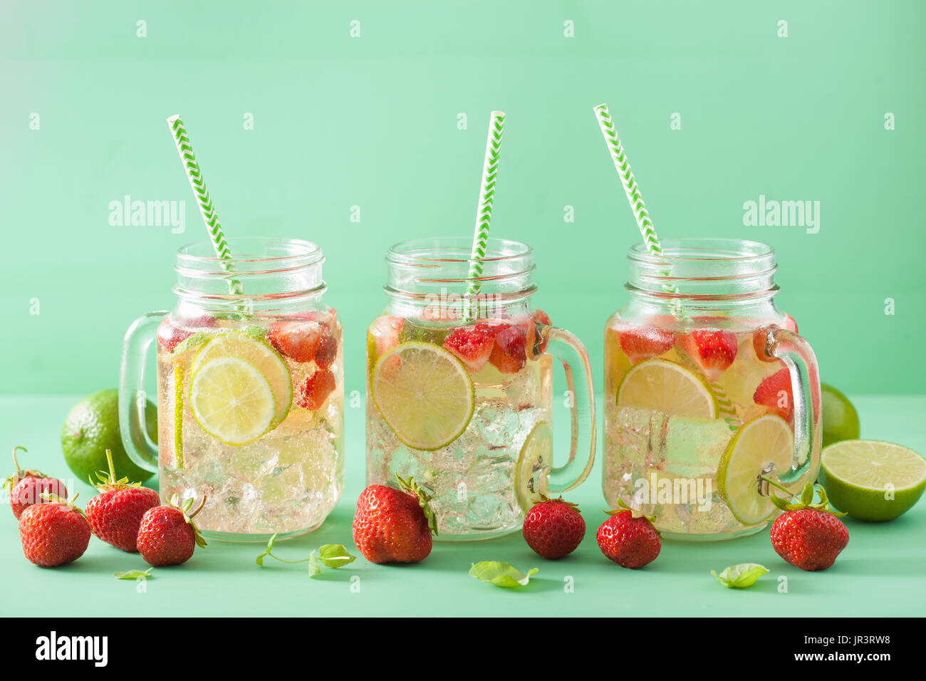 refreshing summer lemonade with strawberry and lime in mason jar - Stock Image