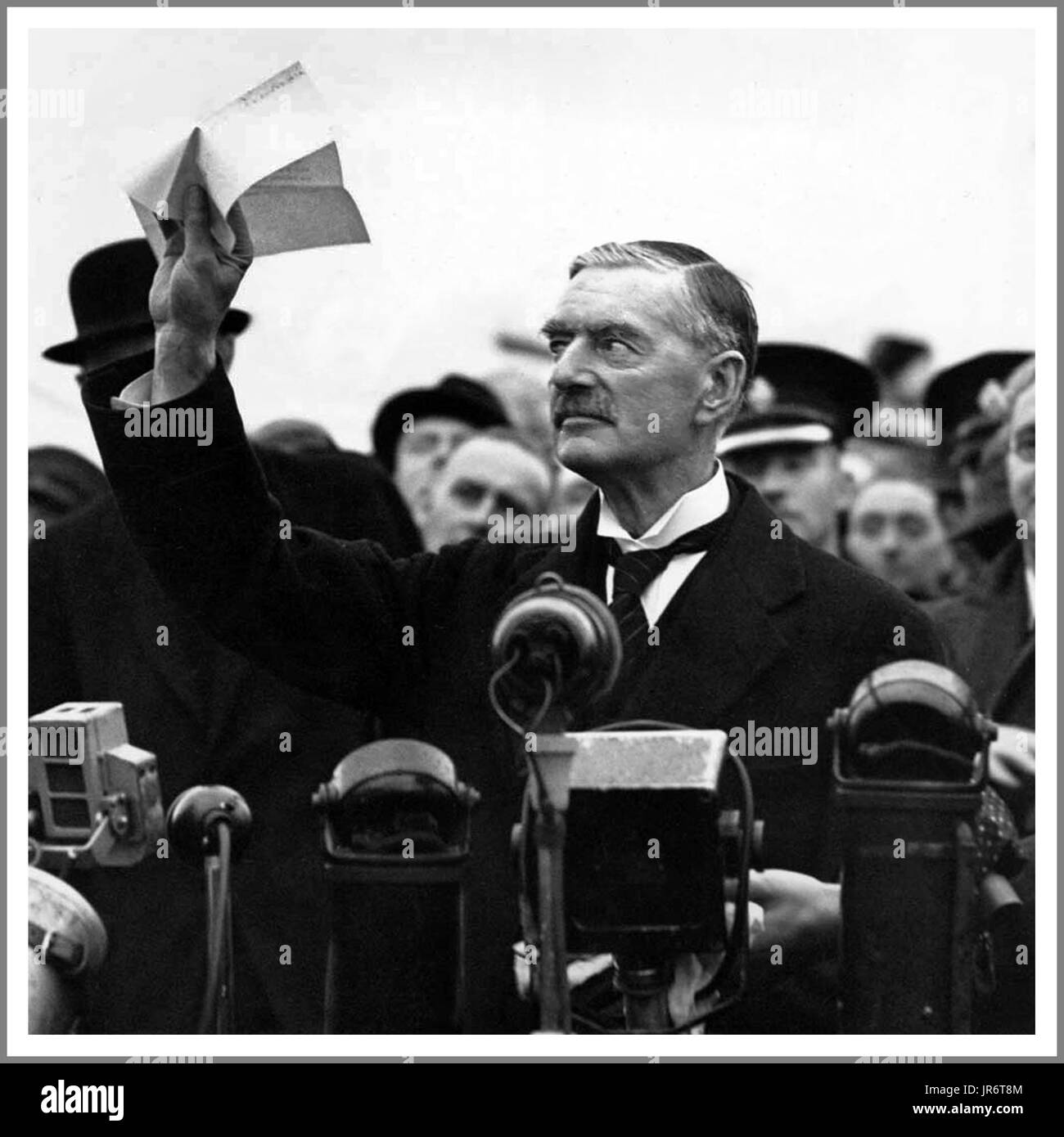 Neville Chamberlain holds 'the' piece of paper proudly aloft signed by both Hitler and himself on his return from Stock Photo