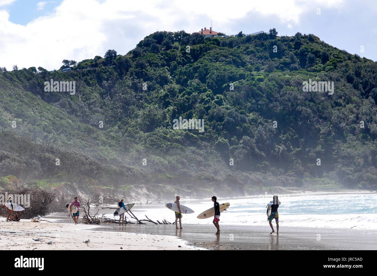 surfers-standing-on-the-beach-holding-their-surfboards-at-tallow-beach-JRC5AD.jpg