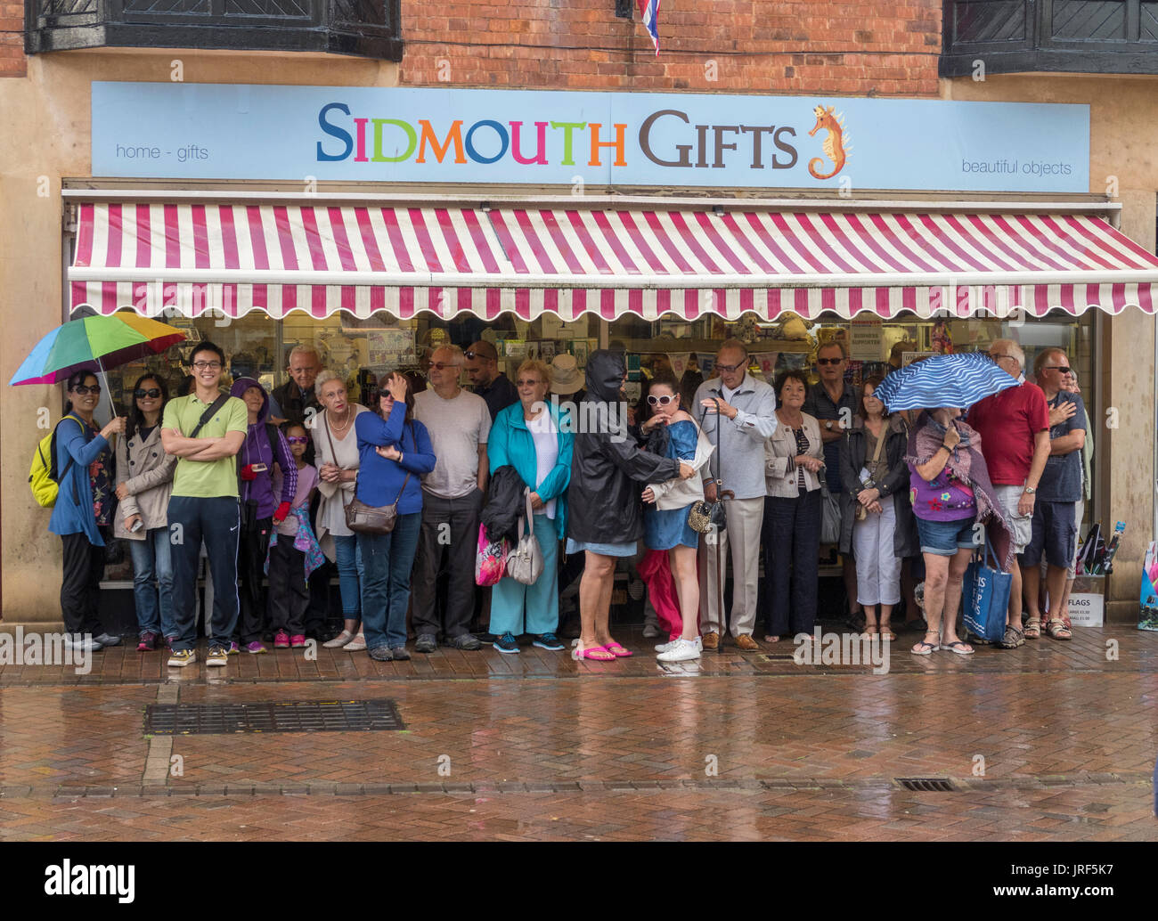 A crowd of people huddle together and shelter from the rain under a shop awning in Sidmouth, Devon. Stock Photo