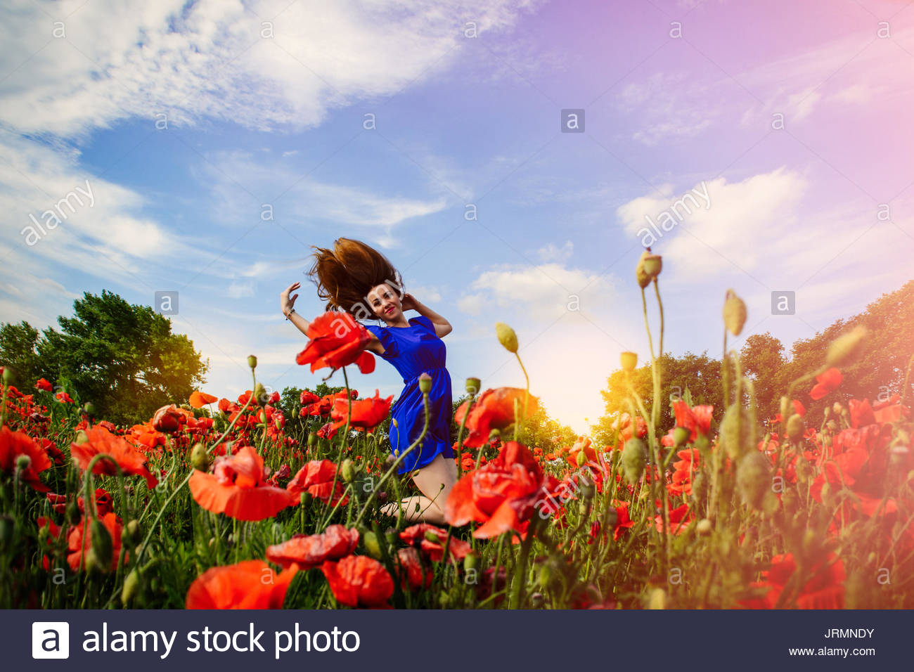 Girl jumping out of flowers - Stock Image