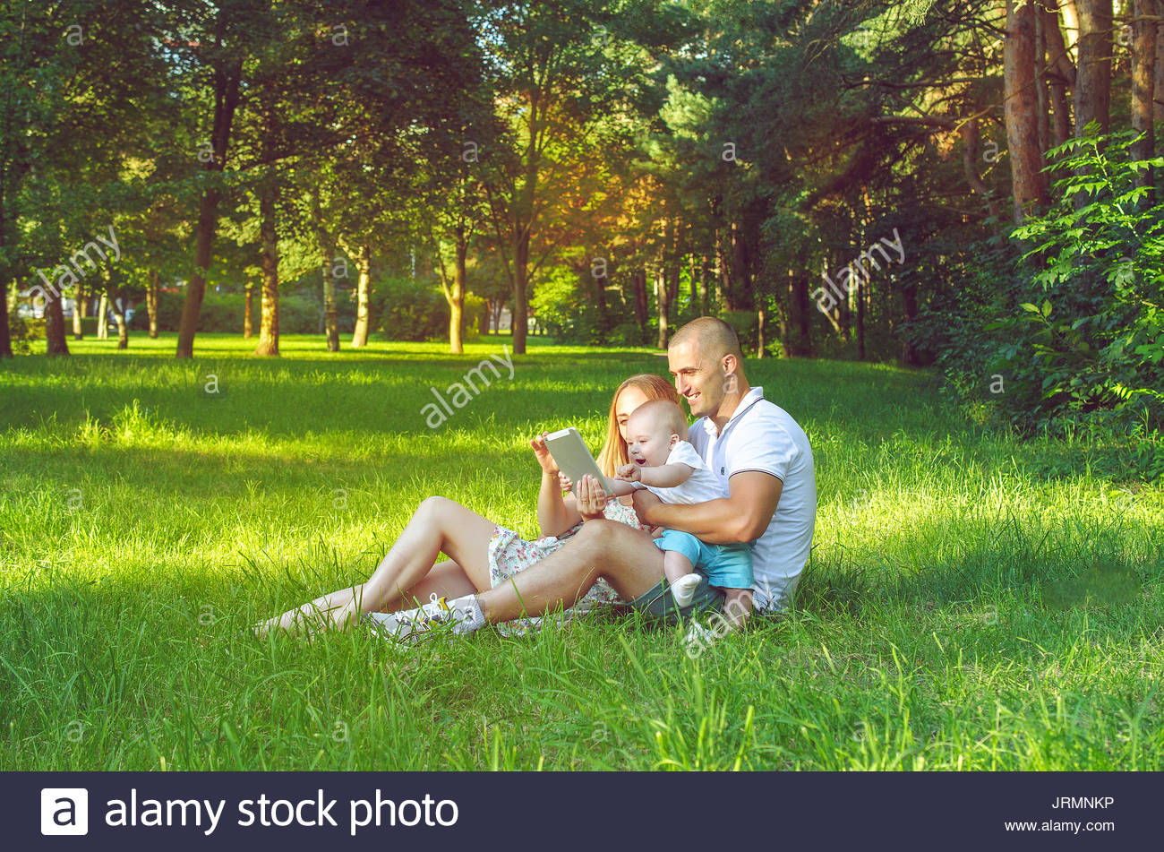 Family spending time with a tablet on nature in summer - Stock Image