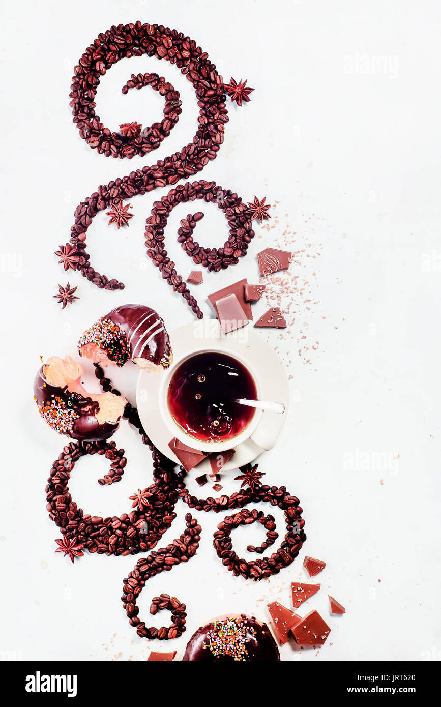 Coffee grains lying in the shape of a swirl with the cup, cinnamon, anise stars and donuts on a white background - Stock Image