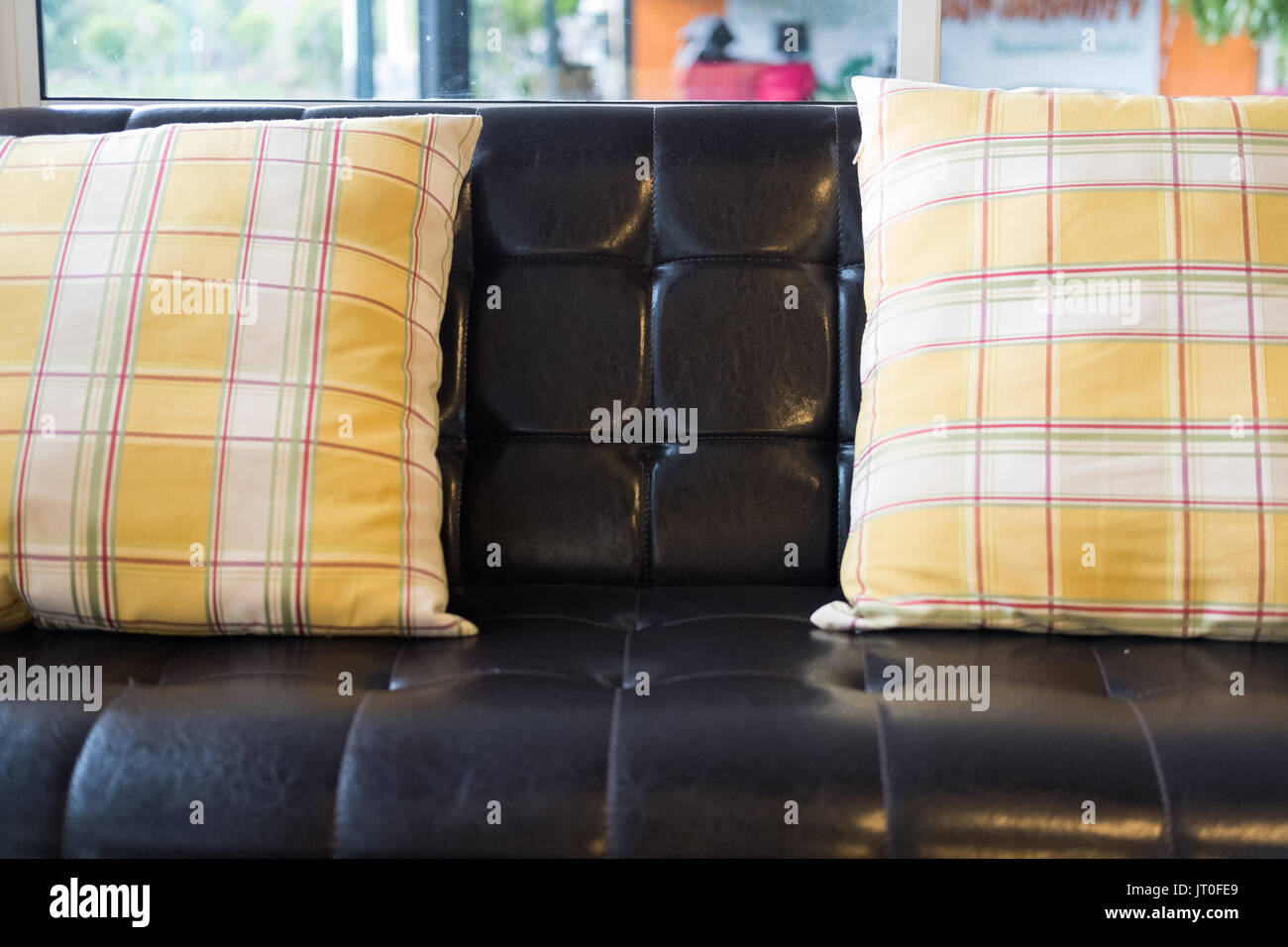 Yellow Fabric Pillow And Brown Leather Sofa Near Window At