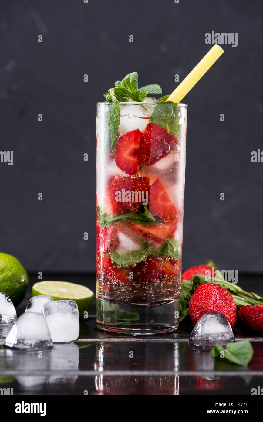 strawberry lemonade in glass with ice cubes, cocktail bar background concept - Stock Image