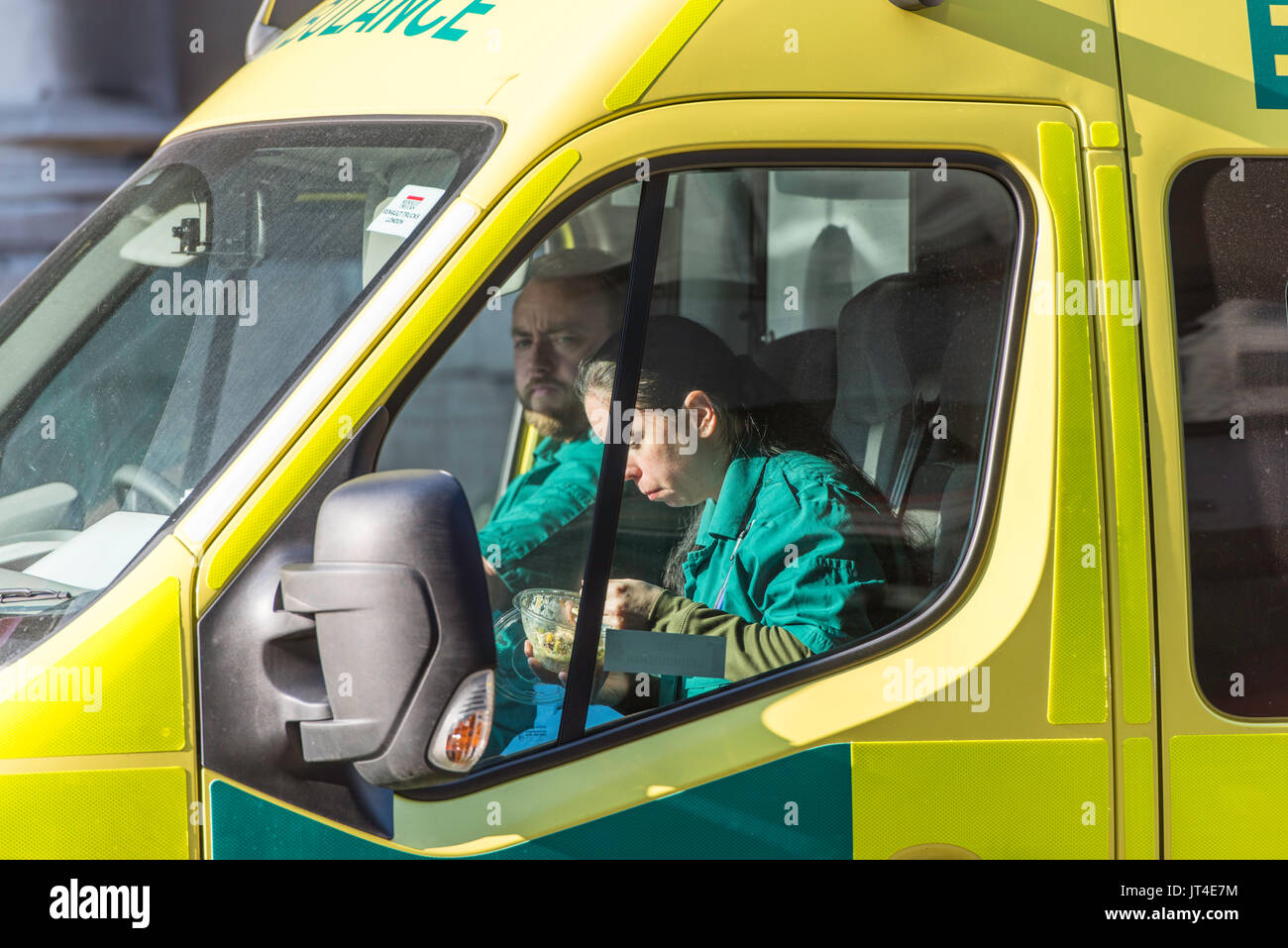 Ambulance stationary in traffic in London, UK. The female paramedic is eating her lunch in the passenger seat. - Stock Image