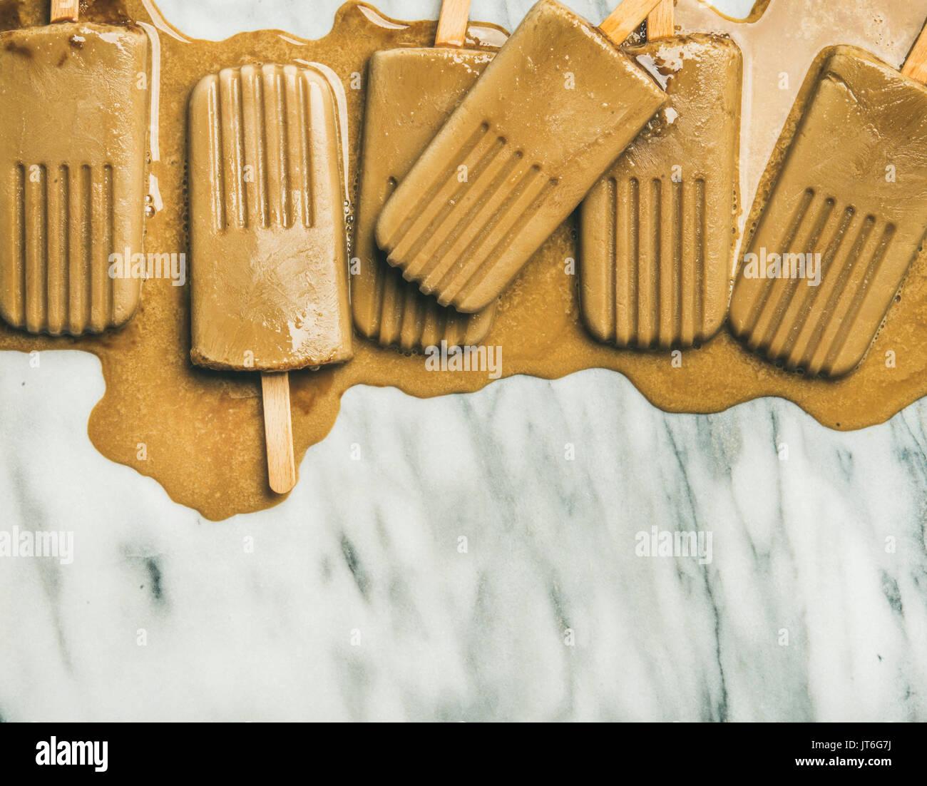 Summer healthy vegan frozen dessert. Flatlay of melting coffee latte popsicles over light grey marble background, - Stock Image