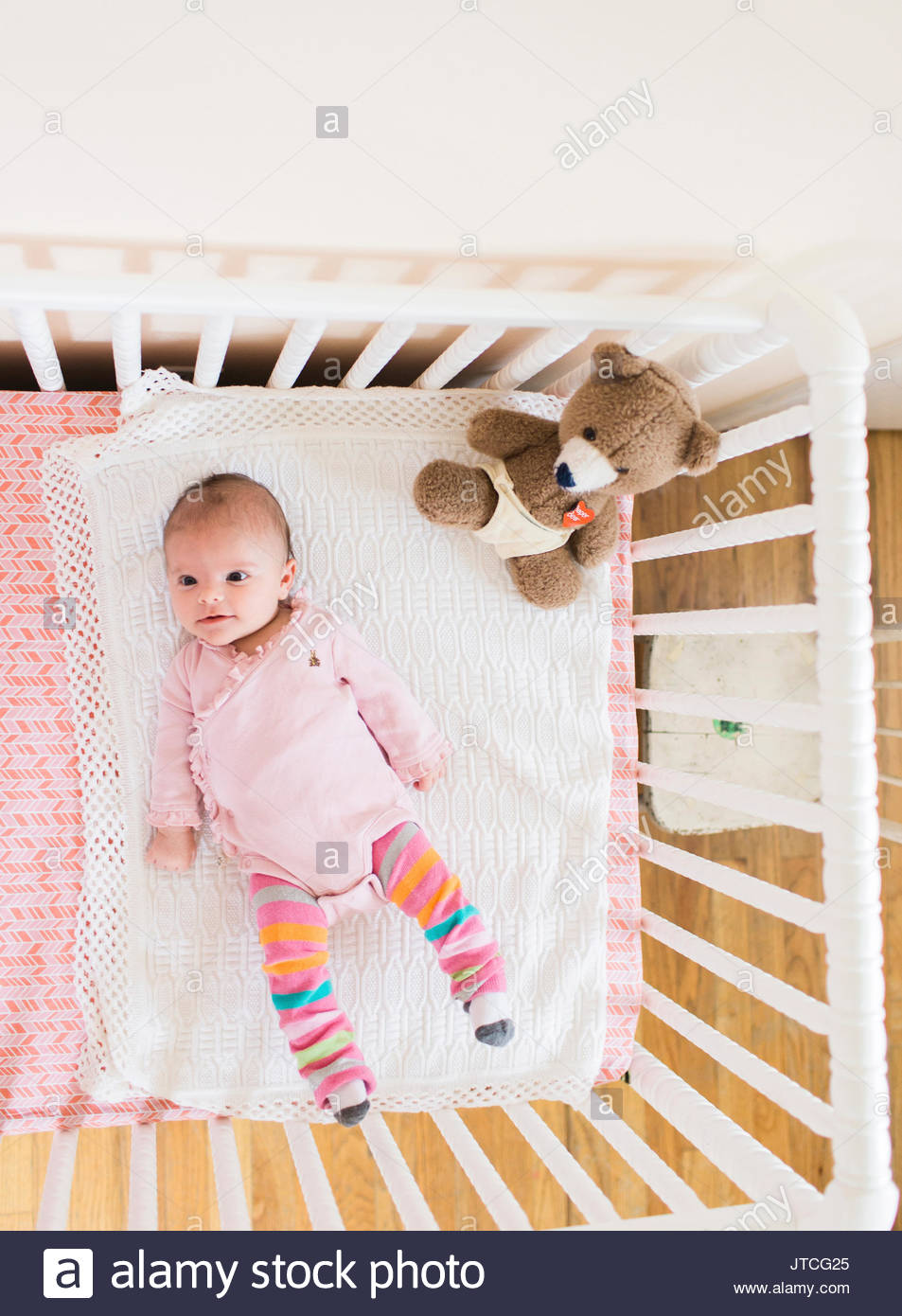ef2be2f4f High angle view of smiling baby wearing pink onesie lying on her back in a  white crib, teddy bear sitting in corner. Mint Images Limited / Alamy Stock  Photo