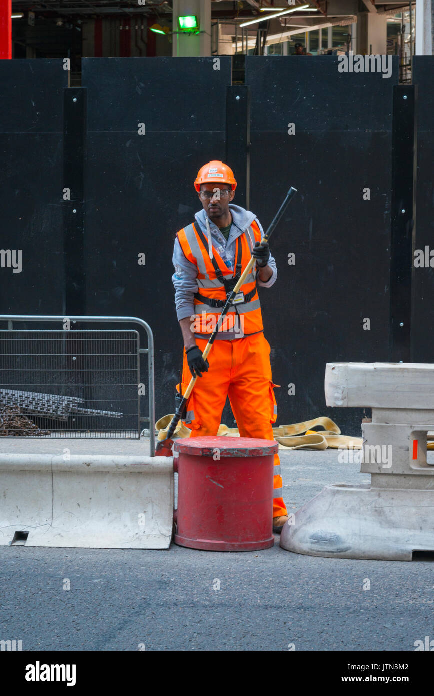UK London City Lime Street British workman high vis jacket trousers safety helmet glasses standing looking pole - Stock Image