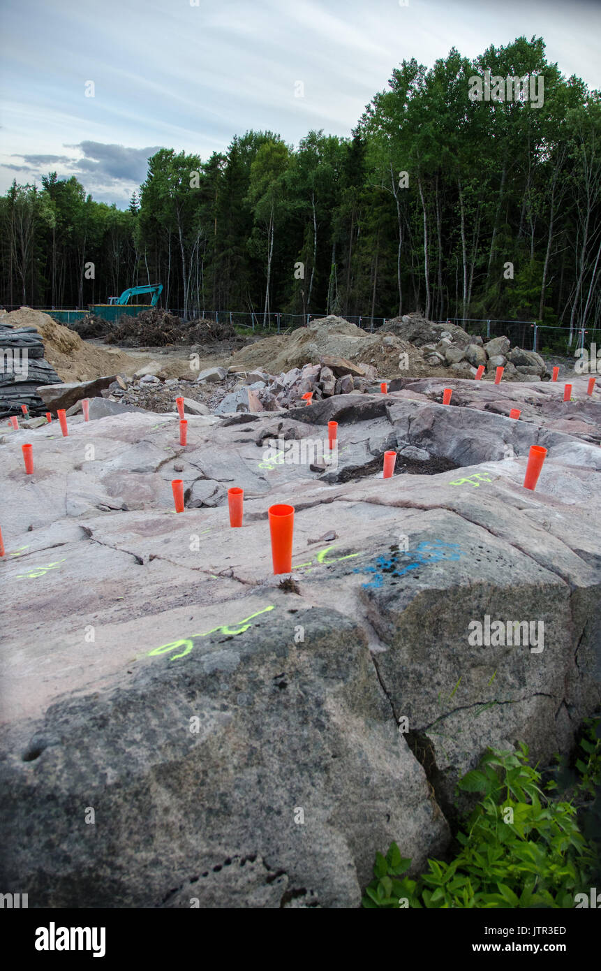 Drilled holes with red pipes to detonate with dynamite and clear the rock for construction. Stockholm, Sweden. - Stock Image