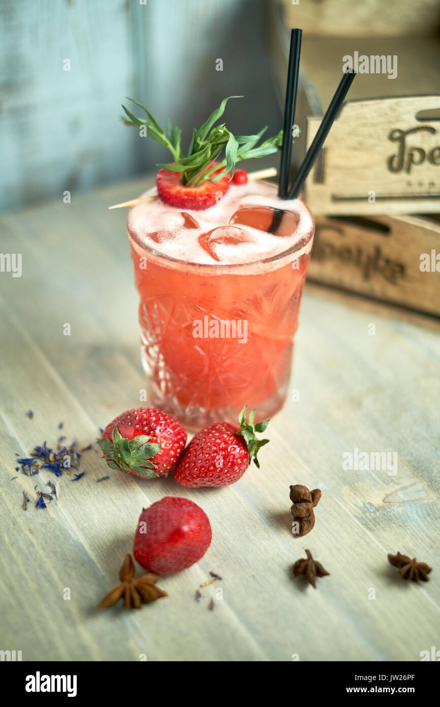 Strawberry lemonade with lime and ice in mason jar on a wooden table jpg - Stock Image